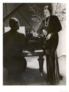 man-plays-a-piano-and-looks-up-at-a-glamorous-woman-in-a-long-dress_i-G-17-1748-LGU3D00Z